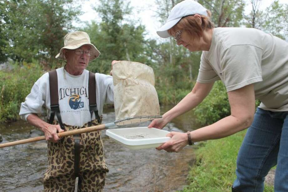RIVER SAMPLES: MRWA Secretary Doug Trembath dumps a scoop of water and river mud into a tray held by MRWA volunteer Jean Mortensen. The pair examined samples from the river on Thursday to look for different species of macroinvertebrates that indicate how healthy the river is. (Herald Review photo/Whitney Gronski-Buffa)