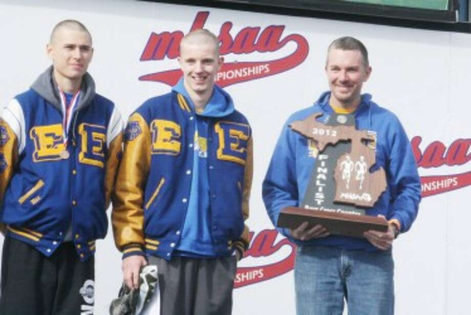 SPECIAL MOMENT: Evart cross country coach Andy Eichelberger holds the Division 4 state runner-up trophy Saturday while Max Hodges (left) and David Zinger enjoy the moment. (Herald Review photo/John Raffel)