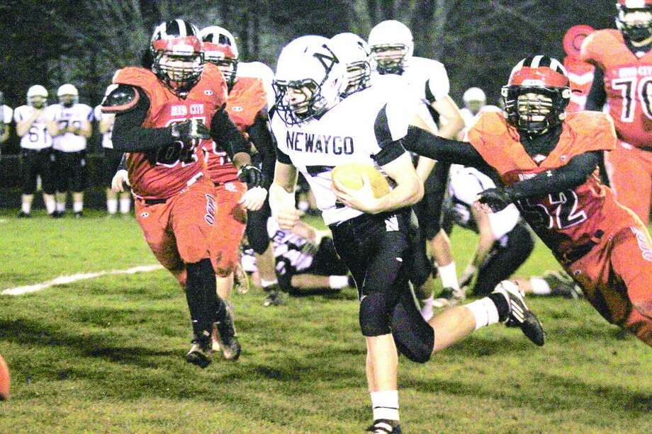 TOUGH RUN: Reed City defensive players, including Jacob Vincent (52), look to make the play against Newyago Friday night. (Herald Review photo/Bob Allan)
