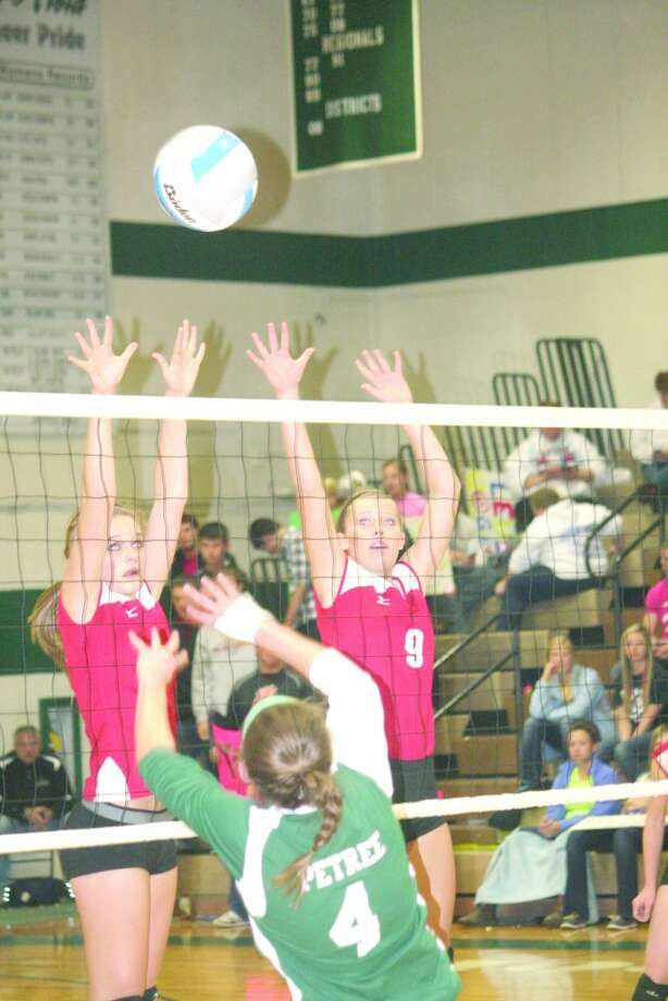 WALL OF DEFENSE: Heather Tacey and Natalie Westhoff try to stop a hit from Clare's Ashley Petree. (Herald Review photo/John Raffel)