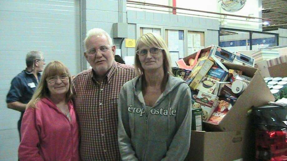 DONATION: Ventra employees Heidi Pontius (left) and Nancy Vokes pose with Sears Food Pantry Facilitator Ken Phillips (center) after revealing two pickup trucks stacked high with food. The members of the women's committee from UAW Local 2270 hosted a food drive for all Ventra employees over the course of two weeks. (Courtesy photo)