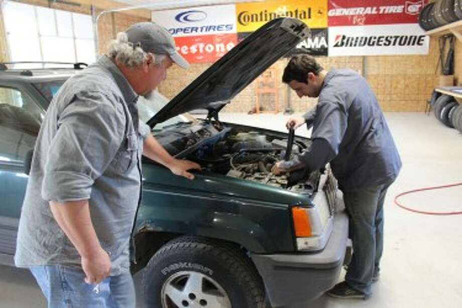 AUTO REPAIR: Chuck Leutz (left) and his son, Ben, work on a Jeep Grand Cherokee at Leutz's Pro Fix in Evart. The business strives to uphold a standard of integrity. (Herald Review photo/Sarah Neubecker)