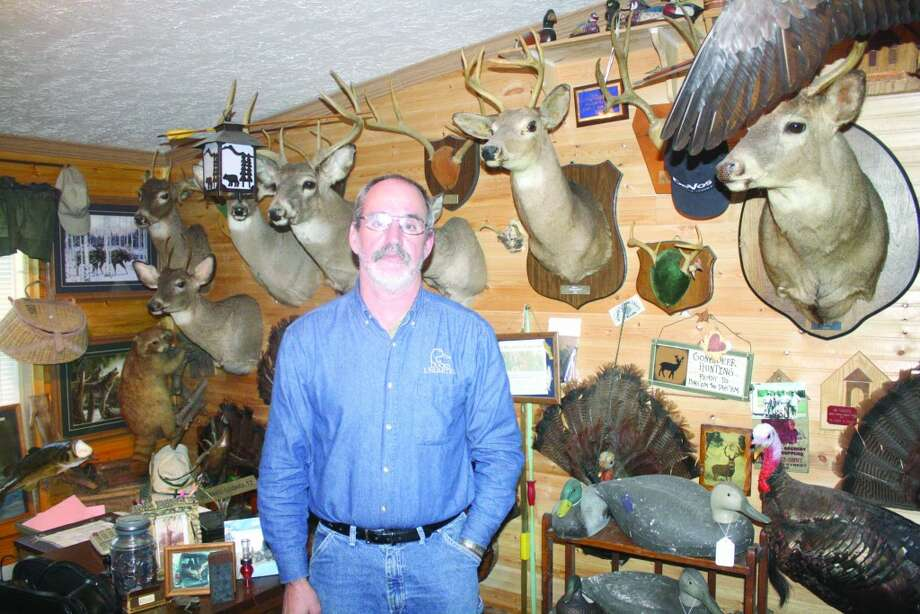 TROPHY WALL: Howie Lodholtz of Chase stands in front of some of his trophies hanging on the wall at his home. (Herald-Review/John Raffel)