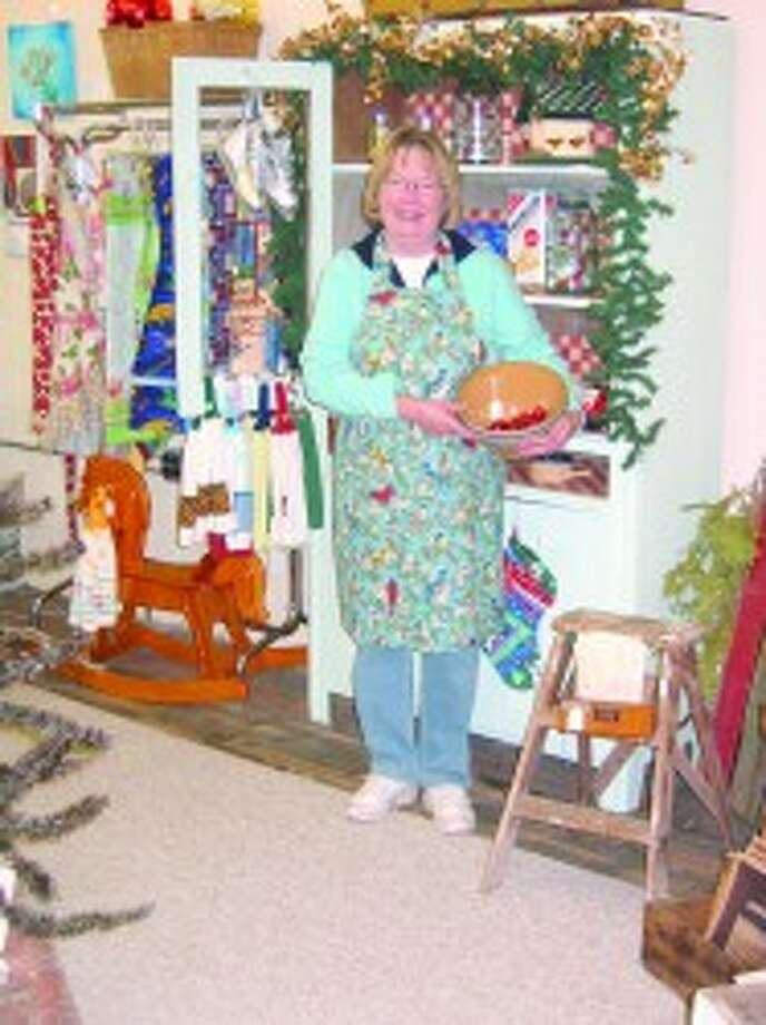 PROUD MEMBER: League member Renee Tolgo, modeling a handmade apron, holds a vintage mixing bowl. (Courtesy photos)