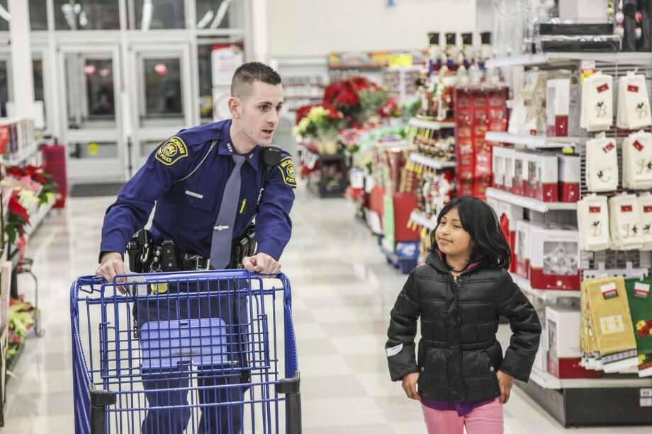 NEW FRIENDS: Michigan State Police Officer Brian Lucha talks with Eiyan, 8, about what to get her cousin and brother at the first Shop with a Hero event Tuesday evening at Meijer. Ten children were nominated by their school counselors and given $90 to shop with a local policeman or firefighter. (Pioneer photos/Justin McKee)