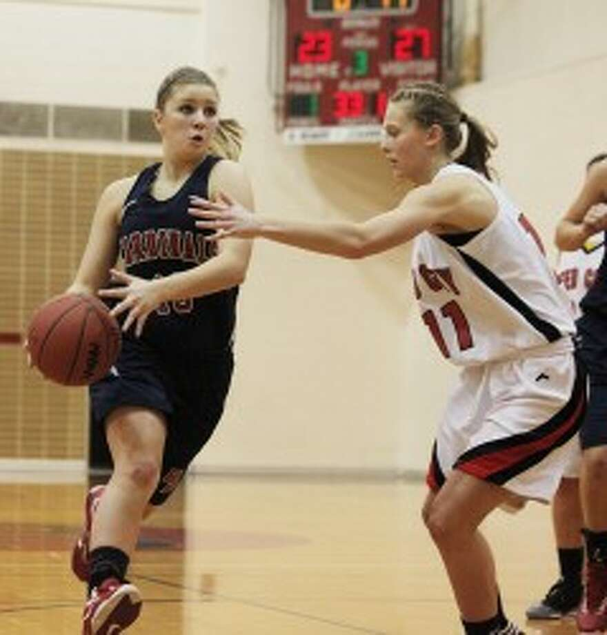 TO THE BUCKET: Big Rapids' Kasey Woodworth (left) tries to drive past Reed City's Natalie Westhoff during Friday night's girls basketball action at Reed City High School. (Pioneer photo/Bob Allan)