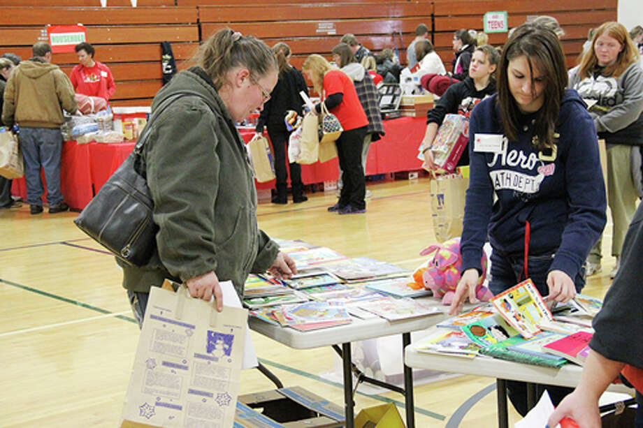 GIFTS FOR ALL: Individuals peruse items available at the Gifts for Kids Distribution on Saturday at Evart Middle School. The program offers Christmas presents for adults and children from low-income families. (Herald Review photos/Sarah Neubecker)