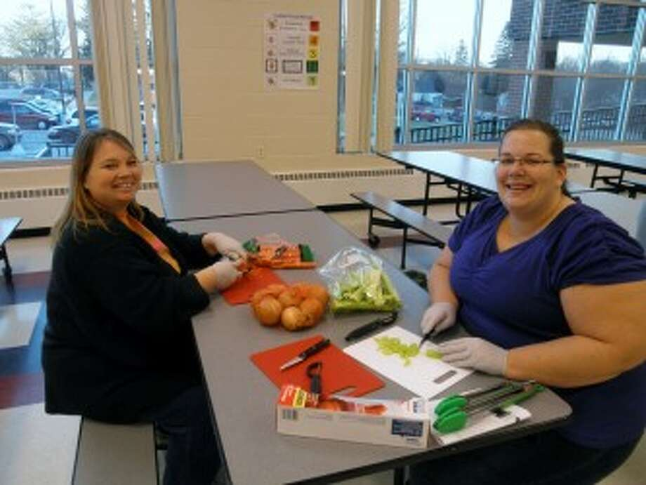 """HEALTHY EATING: Parents chop up vegetables to take home for a soup recipe at a """"meals on a budget"""" parent workshop at G.T. Norman. A dietitian from Spectrum Health Reed City Hospital led the workshop, which was sponsored by Blue Cross Blue Shield of Michigan."""