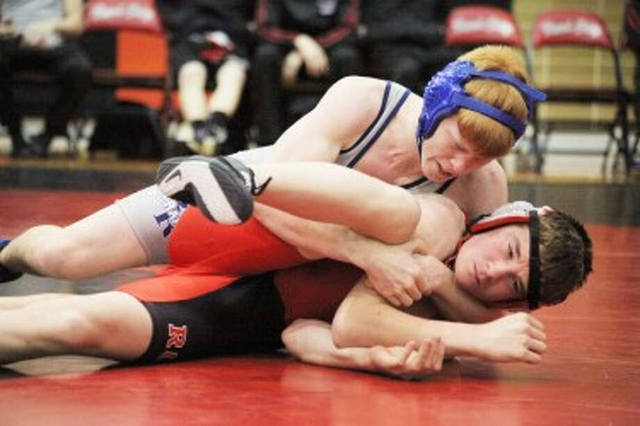 MAKING A MOVE: Big Rapids' Patrick Kettner (top) tries to turn Reed City's Troy Giese in their wrestling match Wednesday. Giese won the match by pin. (Pioneer photo/Bob Allan)