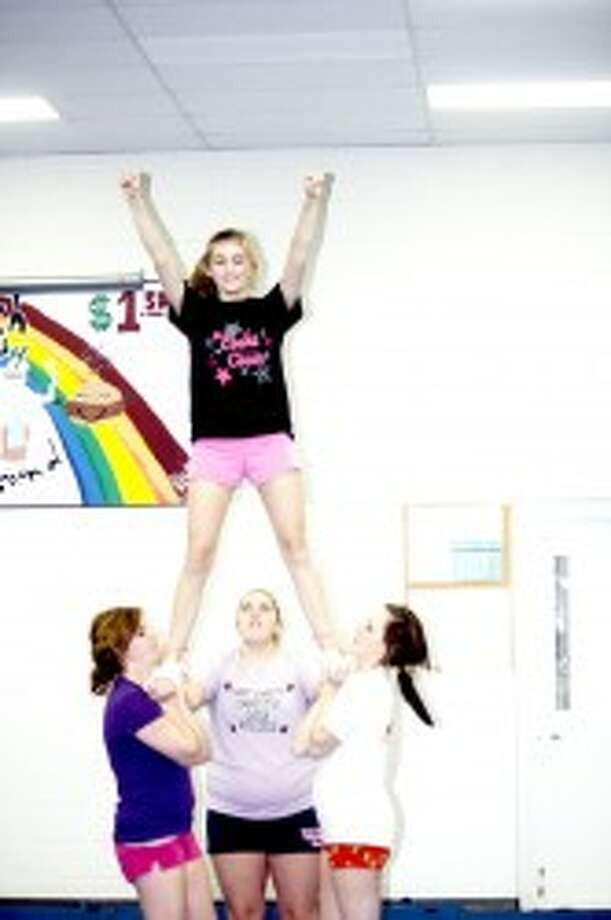 FOCUS: Evart cheerleaders focus on a mount during a recent practice. (File photo)