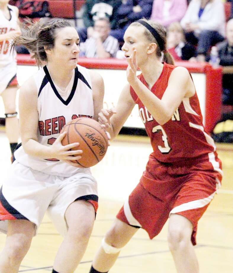 WORKING FOR A WIN: Reed City's Alex Donley (left) tries to get past Holton's Katie Wildfong during Friday's girls basketball contest at Reed City High School. (Herald Review photo/Martin Slagter)