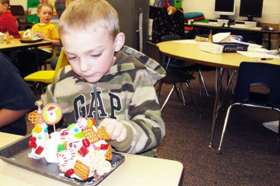 Something tasty: Travis Eisenga from Mrs. Amy Posey's class is in full concentration as he finishes his creation complete with a Gingerbread Man running up the side of his house.