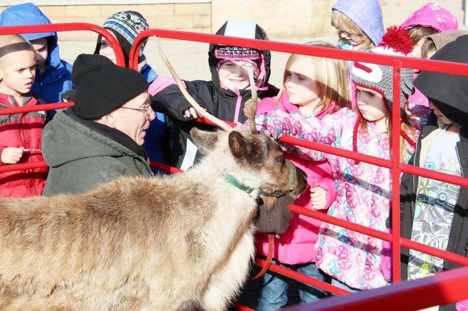 FURRY VISITOR: First-grade students from Evart Elementary School pet Little Prancer, an eight-month-old reindeer from Rooftop Landing Reindeer Farm in Clare. The reindeer visited the students on Dec. 19. (Herald Review photos/Sarah Neubecker)