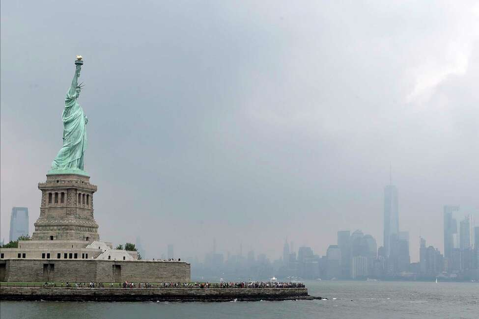 The Statue of Liberty is shown, Wednesday, Aug. 14, 2019, on a stormy afternoon in New York. The words from Emma Lazarus's 1883 poem