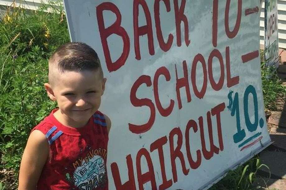 """Hair Dr. in Torrington, located at 1049 East Main St., encouraged children to come in for a $10 haircut to return to school. Brayden showed off his new """"do"""" outside the salon. Photo: Contributed Photo"""