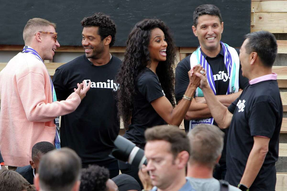 The Seattle Sounders ownership group, including new additons Russell Wilson, Ciara, Macklemore and Terry Myerson, greet each other as they gather with players and coaches at Yesler Terrace Park to celebrate local youth and community at the RAVE Foundation's soccer field, which was built last year, Monday, Aug. 19, 2019.