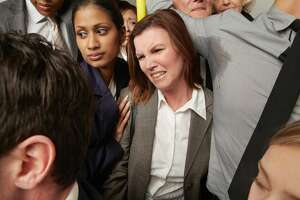Stock photo of a woman annoyed on a crowded train.