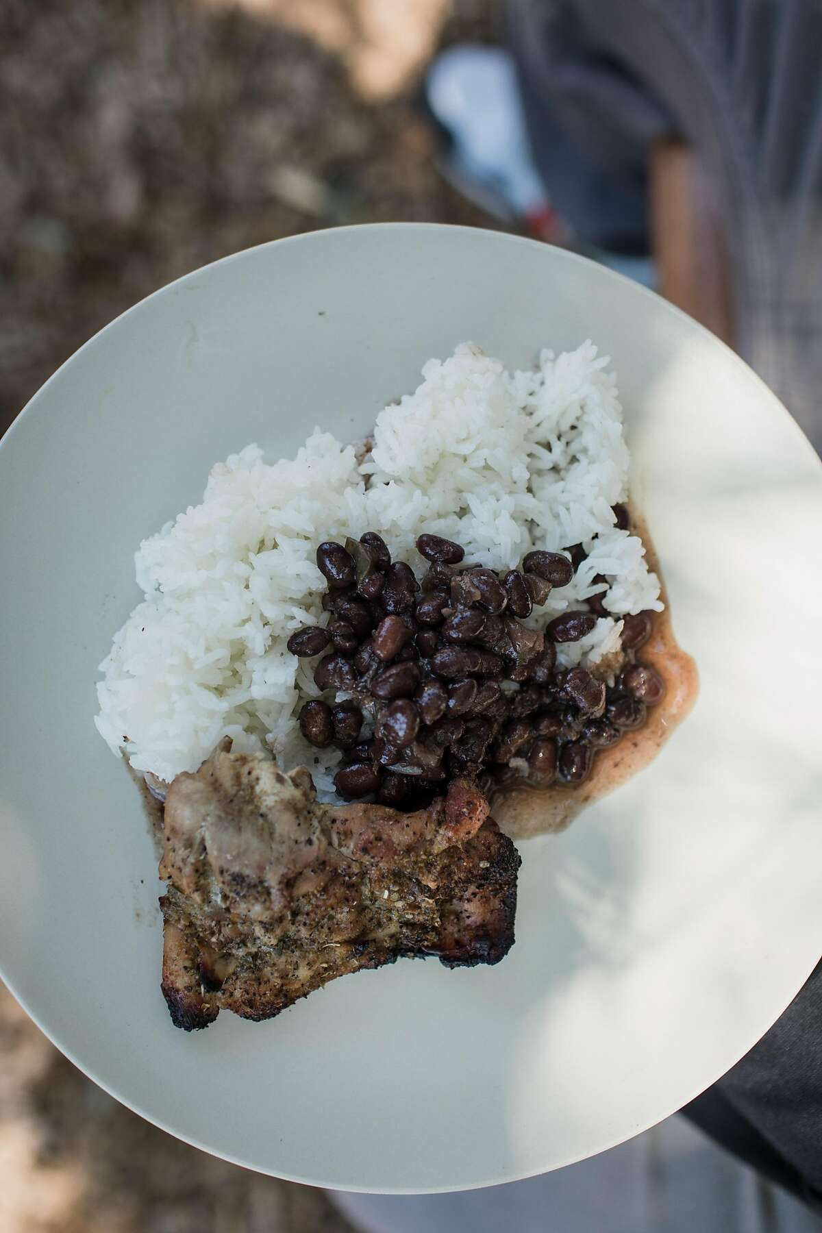 A Dozen Cousins' Cuban black beans served with pollo asado and white rice on June 17, 2019 in Berkeley, California. Cuban black beans are typically made with white sugar and white vinegar, but Dozen Cousins uses apple cider vinegar and tomato paste for the same flavor without added sugar.