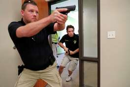 In this July 21, 2019 photo, Trainees Chris Graves, left, and Bryan Hetherington, right, participate in a security training session at Fellowship of the Parks campus in Haslet, Texas. An industry has sprung up following mass shootings at houses of worship around the country to train civilians to protect their churches with the techniques and equipment of law enforcement. (AP Photo/Tony Gutierrez)