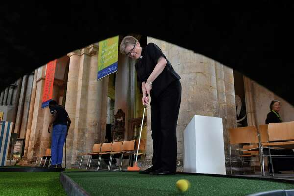 Canon for Mission and Growth, The Reverend Rachel Phillips plays on the bridge-themed mini-golf course set up in the nave of Rochester Cathedral in Rochester, southeast England, on August 6, 2019. - The nave of the medieval Rochester Cathedral has temporarily been taken over by a bridge-themed adventure golf course designed to encourage young people to learn more about the engineering behind bridges and to encourage visitors and strengthen historic links with the community. (Photo by Ben STANSALL / AFP)BEN STANSALL/AFP/Getty Images