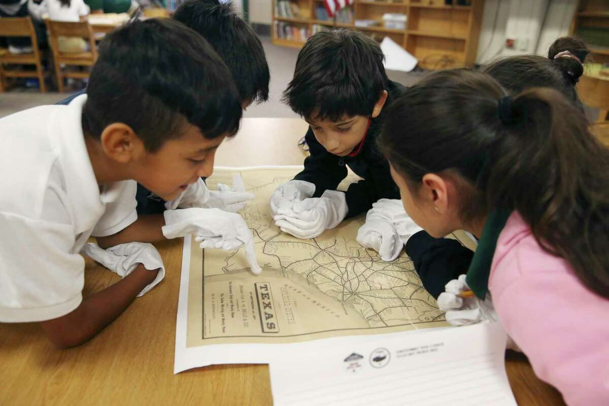 Dante Barrera, 9, center, studies an 1887 Texas railroad map with fellow students during a lesson by Texas Land Commissioner George P. Bush at Storm Relay Lab Elementary School on Monday. Bush gave a lesson to two fourth grade classes at the school. Students were also able to handle a Mexican Army cannonball that is thought to date back to the Battle of the Alamo. Bush also visited Hillcrest Elementary School.
