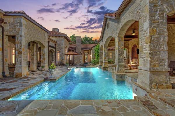 """607 Bentley Manor, Shavano Park TX, 78249 An unparalleled, timeless Masterpiece! """"Casa de Lusso"""" boasts Italian elegance. Luxurious custom home on .82 acre, treed lot. Travertine and hardwood flooring, granite counter tops, 3 stone fireplaces, expansive master suite with separate walk in closets, and his and her baths. Walk through the butler's pantry, wet bar, dishwasher, ice maker. State of the art appliances. Over 100K in artistic hand painted ceilings. Private controlled access gate leads to the 4-car side entry garage. Pool is heated with fountains and spa. Fabulous Pergola outside with fireplace and totally private-manicured landscaping. Contact: Susan Marburger 210-413-0371 Portfolio Real Estate"""