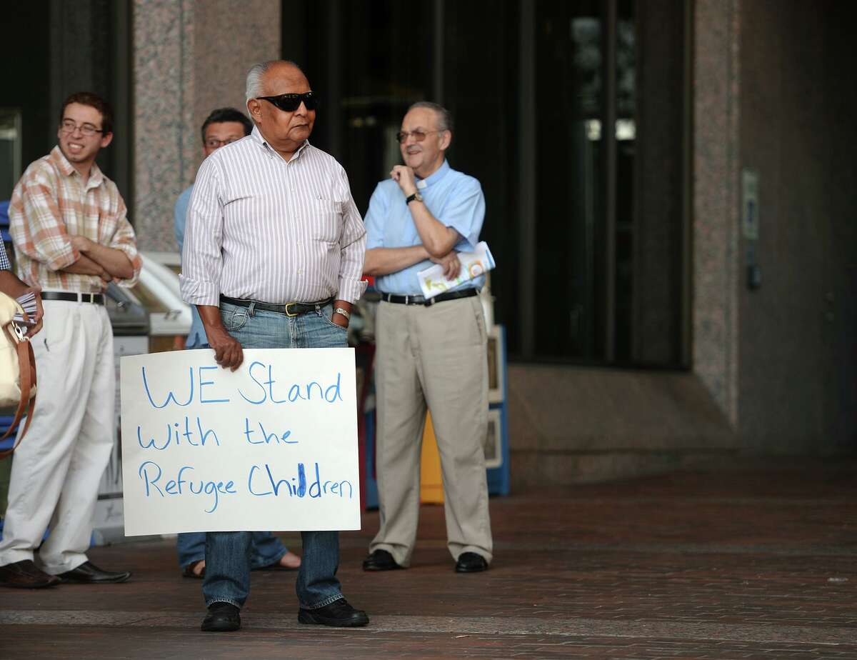 Roberto Flores holds a sign that reads