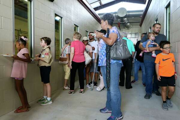 People look at dogs available for adoption during the grand opening celebration of the City of Converse Animal Care Facility at 8755 FM 1516 on Aug. 10.