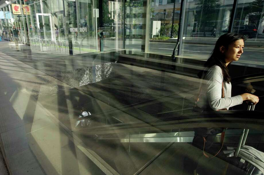 In this Monday, July 15, 2019 photo a passer-by, right, uses an escalator while emerging from a subway station, in Boston's Seaport district. According to the National Association for Business Economics quarterly survey, released Monday, July 29, U.S. business economists expect economic growth to slow this year, and a rising proportion of them think corporate sales and profits will decline. (AP Photo/Steven Senne) Photo: Steven Senne, STF / Associated Press / Copyright 2019 The Associated Press. All rights reserved