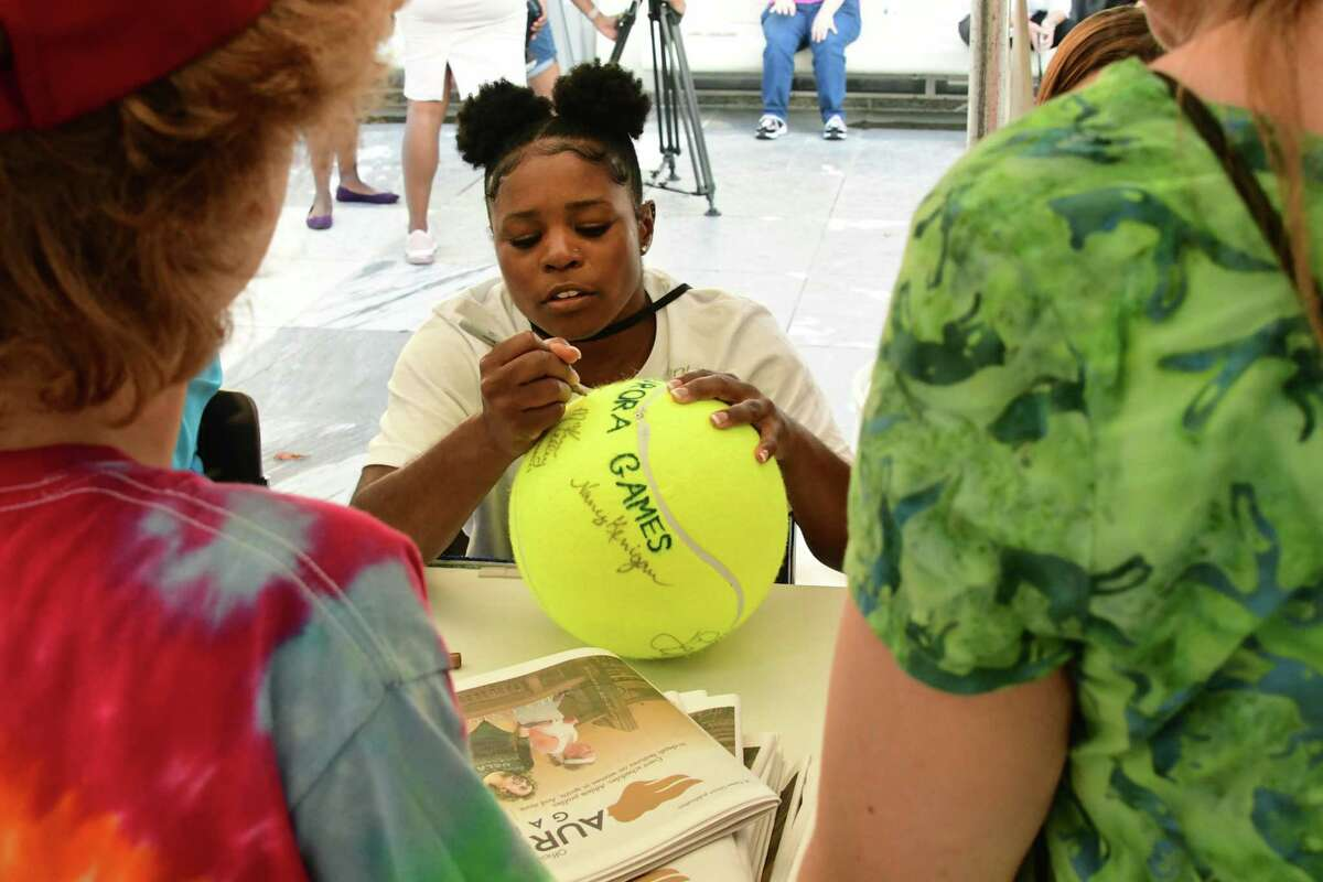 Artistic gymnast Alicia Boren signs a giant tennis ball for Stanley Cornell, 11, of Albany with his mom Joyce at right during the official Aurora Games kickoff ceremony held at the Empire State Plaza on Monday, Aug. 19, 2019 in Albany, N.Y. (Lori Van Buren/Times Union)