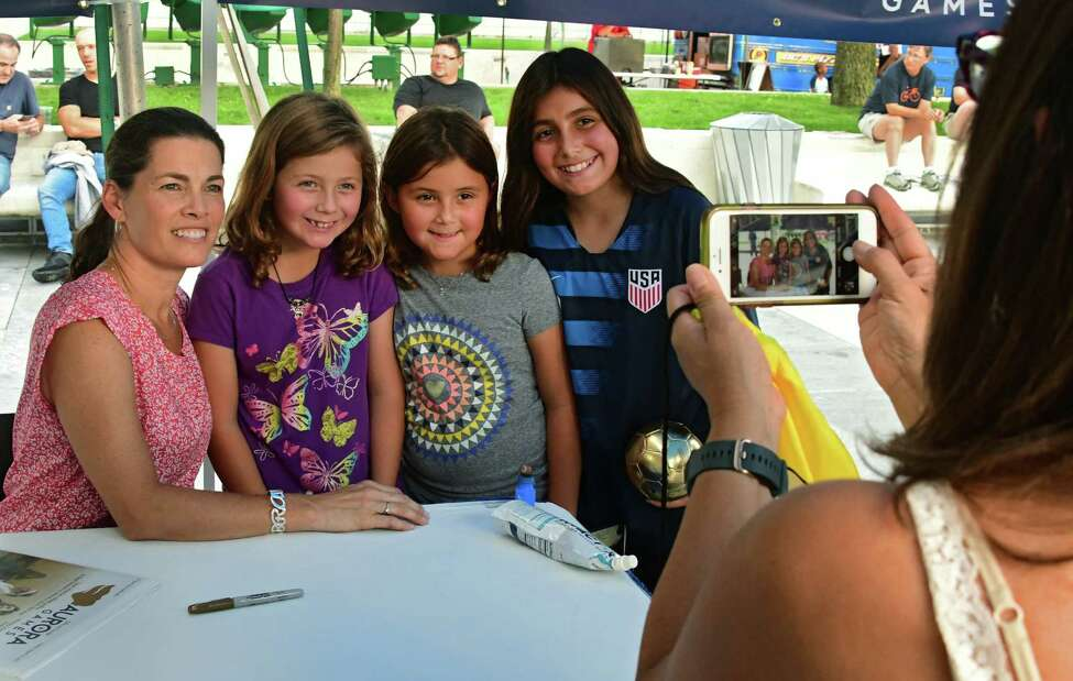 Nelly Garcia, right, takes a photo of olympic figure skater Nancy Kerrigan, left, with her daughters, from left, Vienna, 8, Sophia, 8, and Julia, 11, during the official Aurora Games kickoff ceremony held at the Empire State Plaza on Monday, Aug. 19, 2019 in Albany, N.Y. (Lori Van Buren/Times Union)