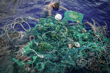 A member of the crew attaches an ocean tracker to a giant mass of netting found in the Pacific Ocean.
