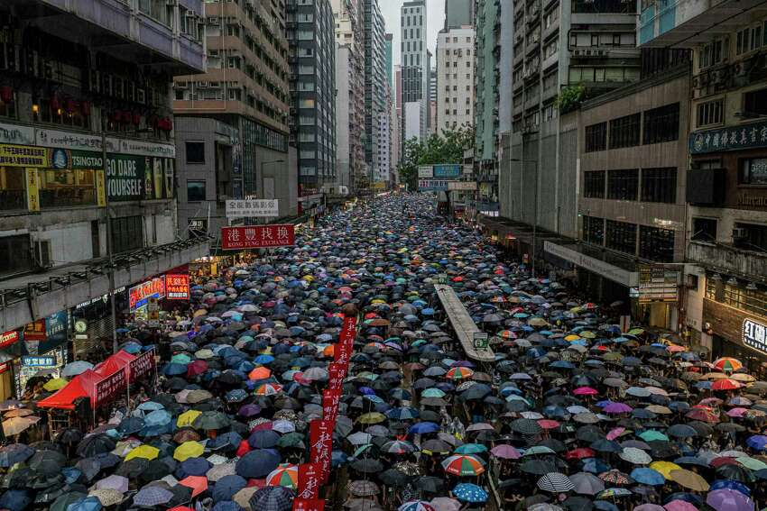 Tens of thousands of protesters march on Sunday, Aug. 18, 2019, in Hong Kong despite a downpour. The protesters defied a police ban on extending the rally beyond Victoria Park. (Lam Yik Fei/The New York Times)