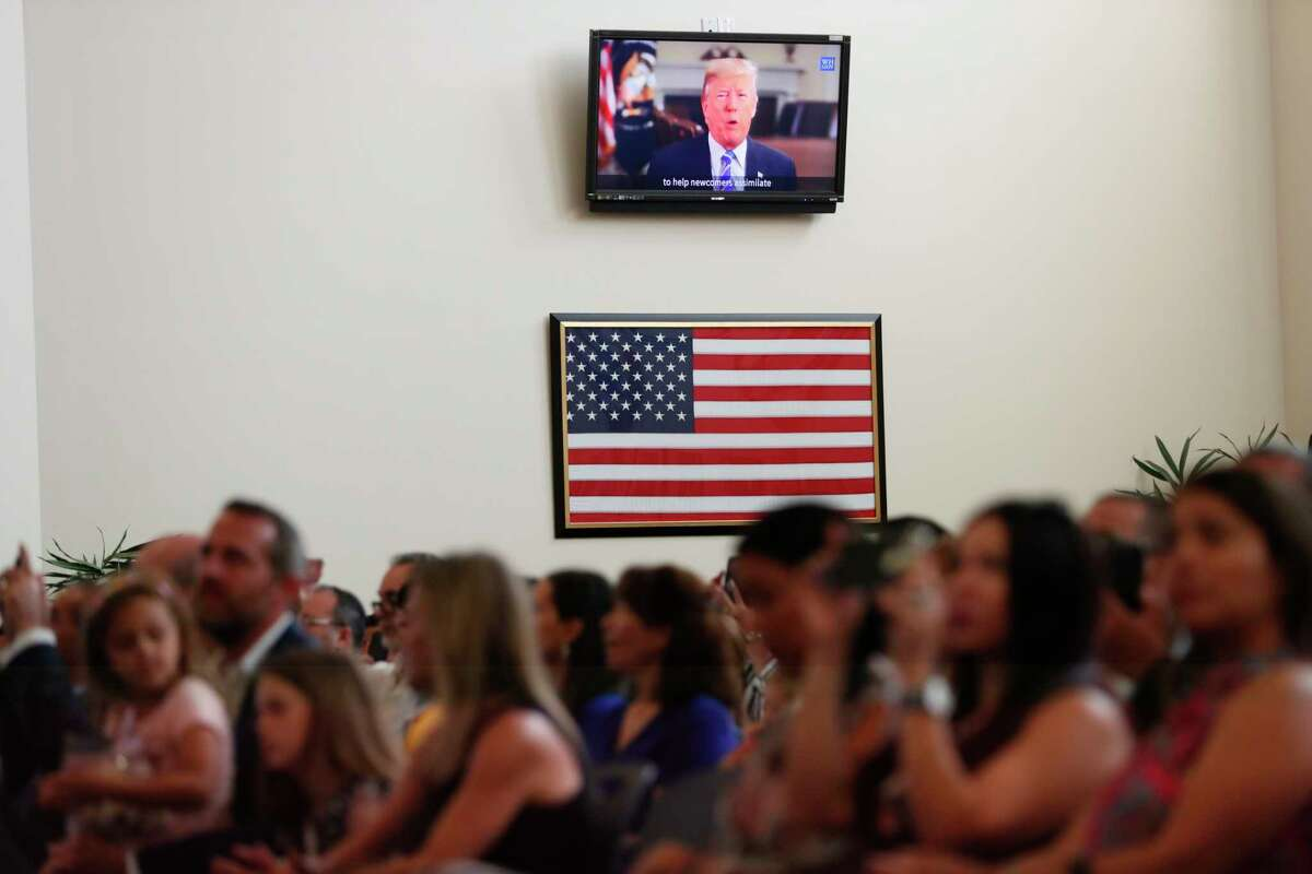 FILE - In this Aug. 16, 2019, file photo President Donald Trump congratulates newly naturalized citizens via a recorded message at the U.S. Citizenship and Immigration Services Miami field office in Miami. Foreign-born residents had higher rates of being employed than those born in the United States last year, and naturalized immigrants were more likely to have advanced degrees than the native-born, according to figures released Monday, Aug. 19, by the U.S. Census Bureau. (AP Photo/Wilfredo Lee, File)