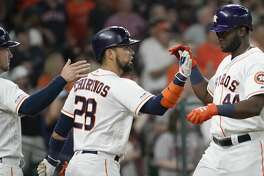Houston Astros Alex Bregman, left, and Robinson Chirinos, center, celebrates with Yordan Alvarez, right, as he scores on a double hit by Yuli Gurriel against the Detroit Tigers during the first inning of MLB game at Minute Maid Park Monday, Aug. 19, 2019, in Houston. Alex Bregman also scored.