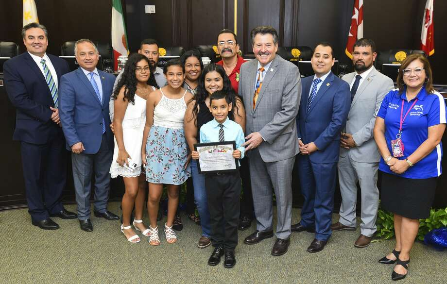 City of Laredo officials, friends and family of Ethan Hernandez gather for a photo as Hernandez is recognized by the City of Laredo for collecting bottle caps to help provide chemo treatment for his basketball coach's late brother, Monday, Aug. 19, 2019, at the City Hall City Council Chambers. Photo: Danny Zaragoza/Laredo Morning Times