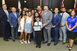 City of Laredo officials, friends and family of Ethan Hernandez gather for a photo as Hernandez is recognized by the City of Laredo for collecting bottle caps to help provide chemo treatment for his basketball coach's late brother, Monday, Aug. 19, 2019, at the City Hall City Council Chambers.