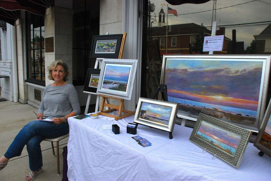 The Art Society of Old Greenwich will be hosting its 68th annual Sidewalk Art Show & Sale September 14-15. Gail Bell with her landscapes at last year's event. Photo: Art Society Of Old Greenwich / Contributed Photo