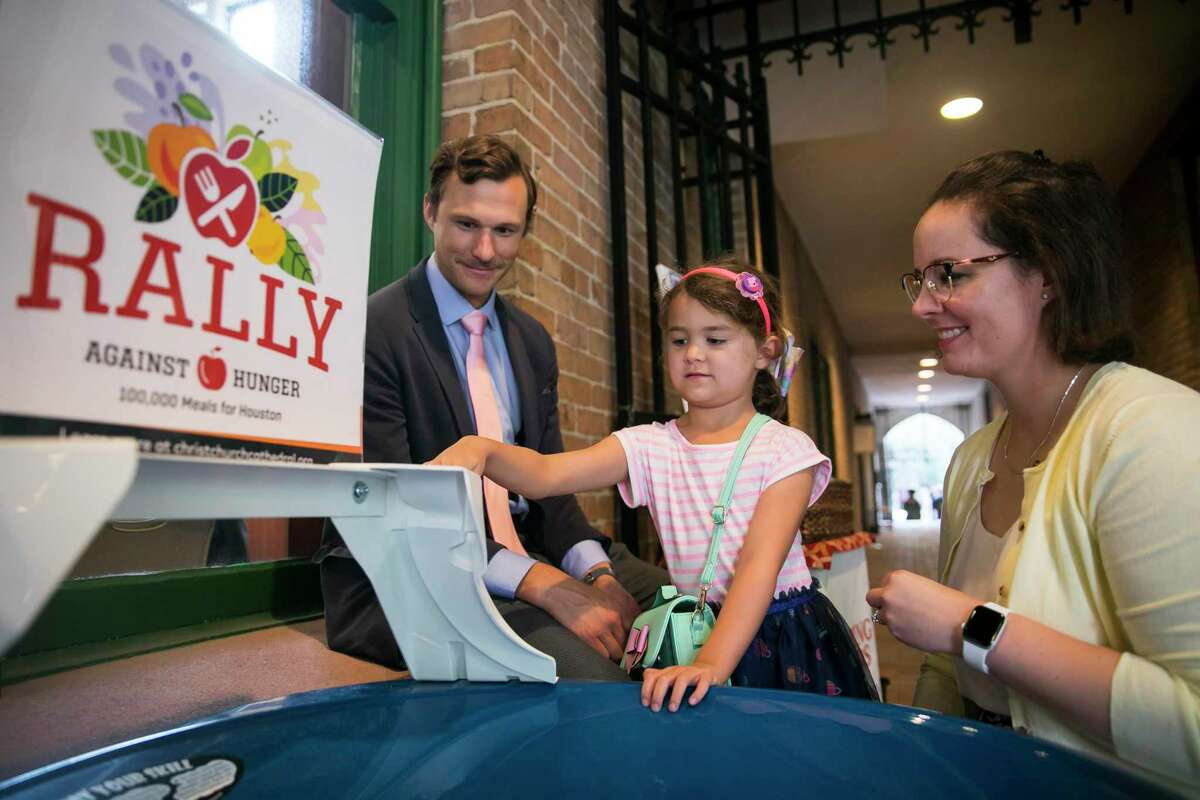 """Five-year-old Lydia Abbott drops coins into a wishing well to raise money for Christ Church Cathedral's first ever """"Rally Against Hunger"""" event during in-between services on Sunday, Aug. 11, 2019, in Houston. The church is raising $40,000 to purchase the supplies to make 100,000 meals for Bayou City Blessings in a Backpack, the Houston chapter of the national organization of the same name."""