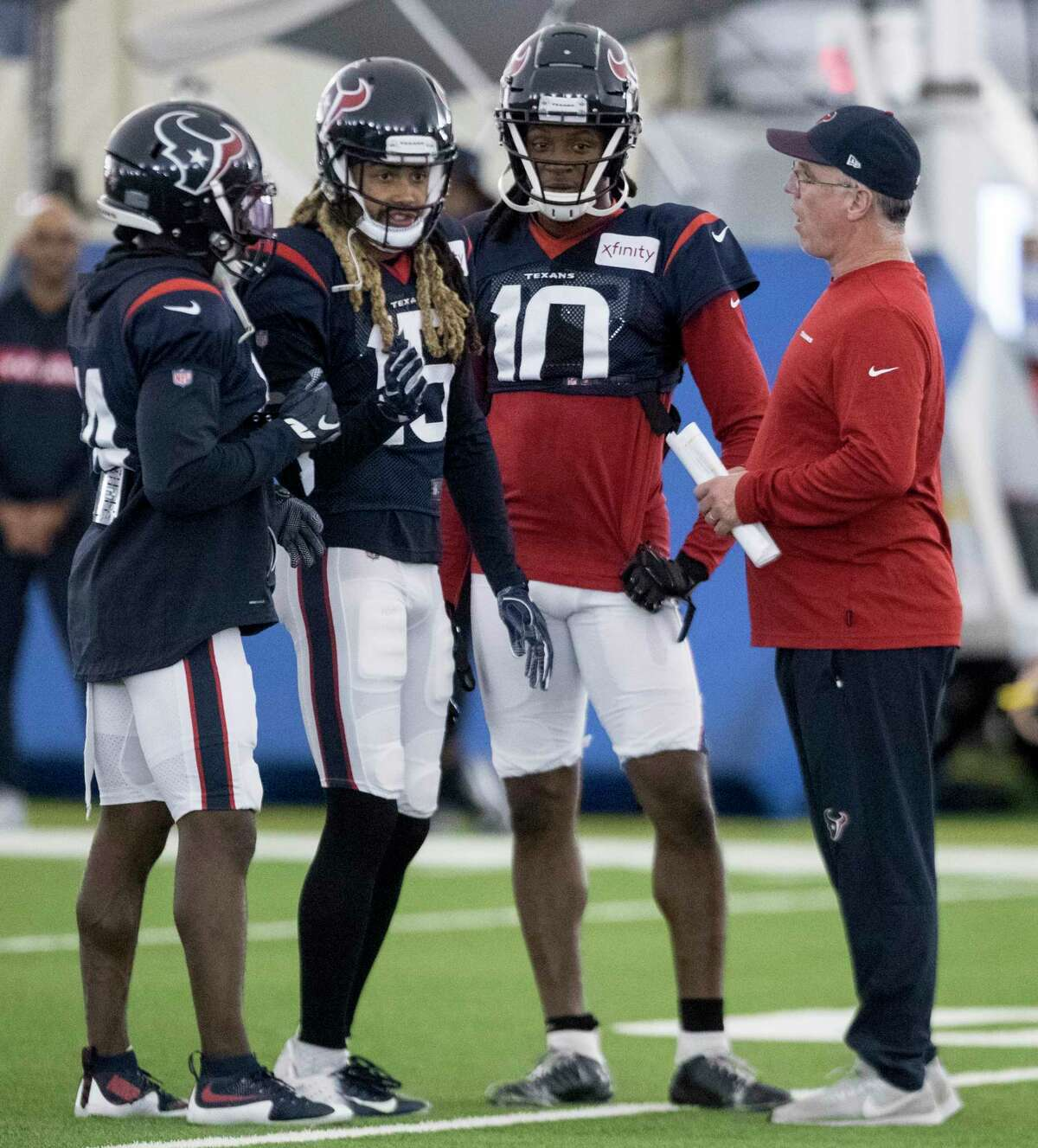 Houston Texans receivers coach John Perry, right, works with wide receivers DeAndre Carter (14), Will Fuller (15) and DeAndre Hopkins (10) during training camp at the Methodist Training Center on Tuesday, Aug. 20, 2019, in Houston.