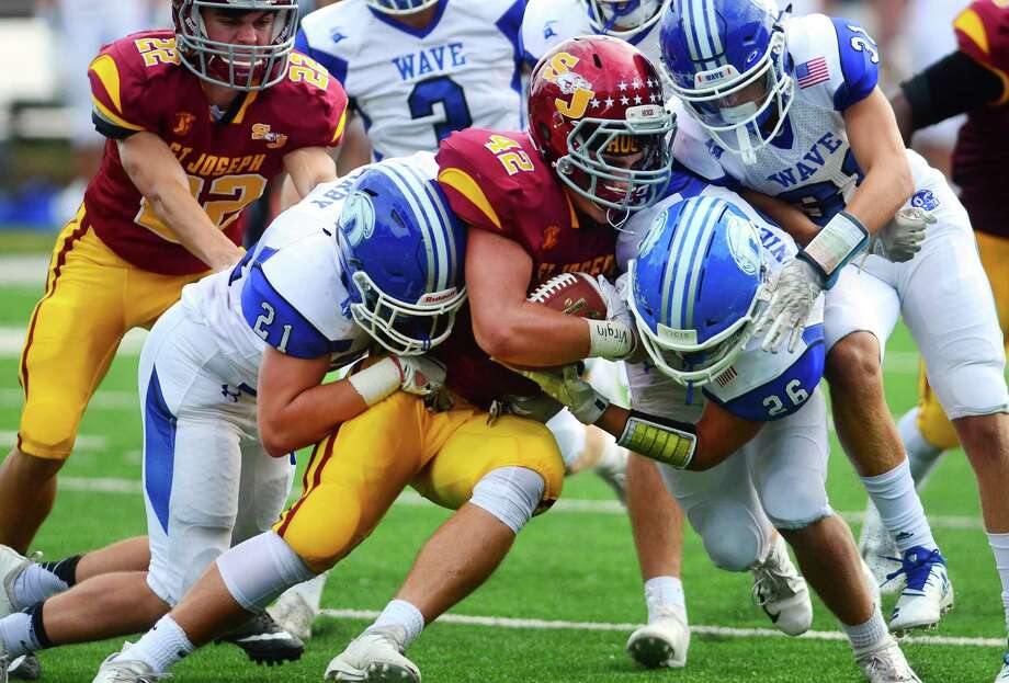 St. Joseph's Cole daSilva (42) is tackled by Darien's Will Kirby, left, and J.H. Slonieski, right, during a game in Trumbull on Sept. 22, 2018. Photo: Christian Abraham / Hearst Connecticut Media / Connecticut Post