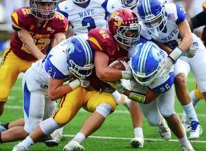 Darien's Will Kirby, left, and John Henry Slonieski, right, tackle St. Joseph's Cole daSilva during a game in Trumbull on Sept. 22, 2018.