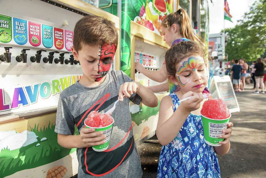 Bobby Prusak, 6, and his sister, Sadie, 4, of Wilton enjoy Italian ice from Kona Ice at the 2nd annual Wilton Food Truck Festival on Aug. 17, at Miller-Driscoll School. The event benefits the Trackside Teen Center. Photo: Bryan Haeffele / Hearst Connecticut Media / Hearst Connecticut Media