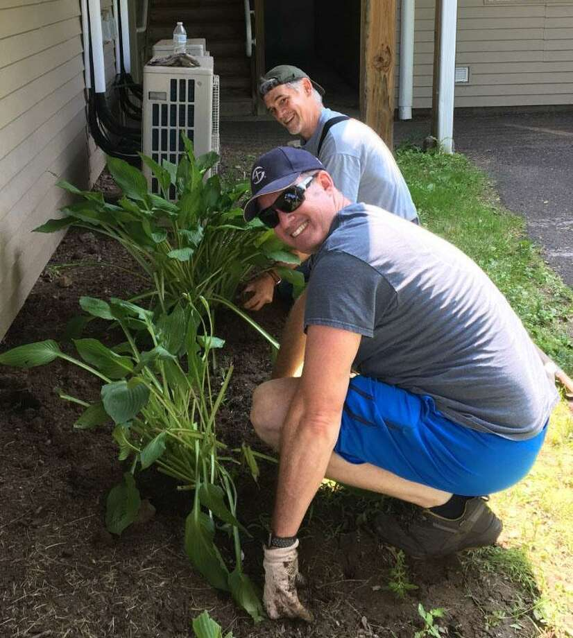 Volunteers Mark Avery and Peter Goodman tend to a flowerbed makeover. Photo: Courtesy Of Justin Gailey / The News-Times Contributed