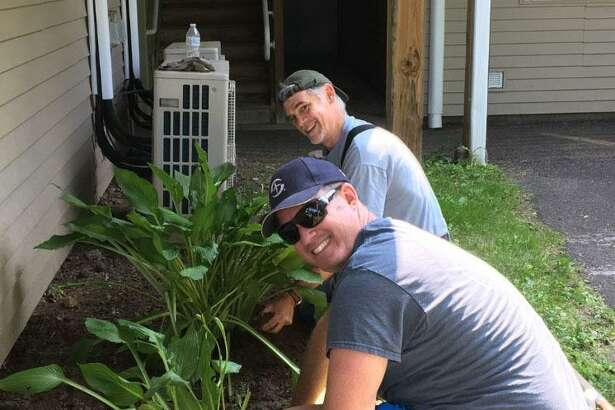 Volunteers Mark Avery and Peter Goodman tend to a flowerbed makeover.