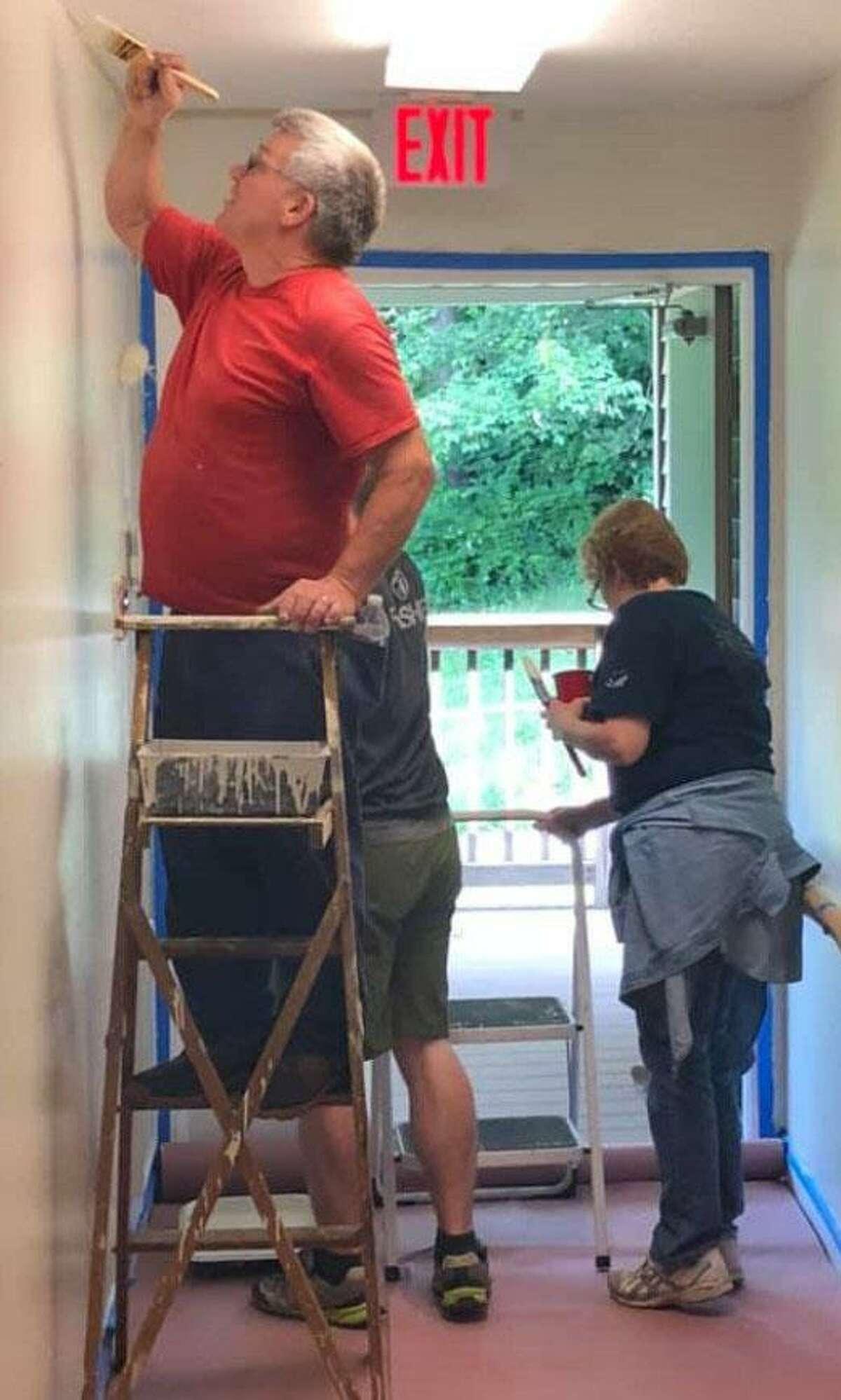 Volunteers George Hipp, Scott Harvey, Wendy Harvey and Zach Terbeek paint a hallway during a recent work day.