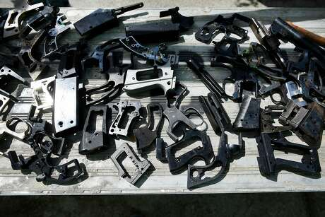 Pieces of disassembled guns sit on a table at American Steel Studios in Oakland, Calif., Saturday April 7th, 2018. The Alameda County District Attorney's Office is partnering with the Robby Poblete Foundation to commission seven sculptures made from disassembled guns.