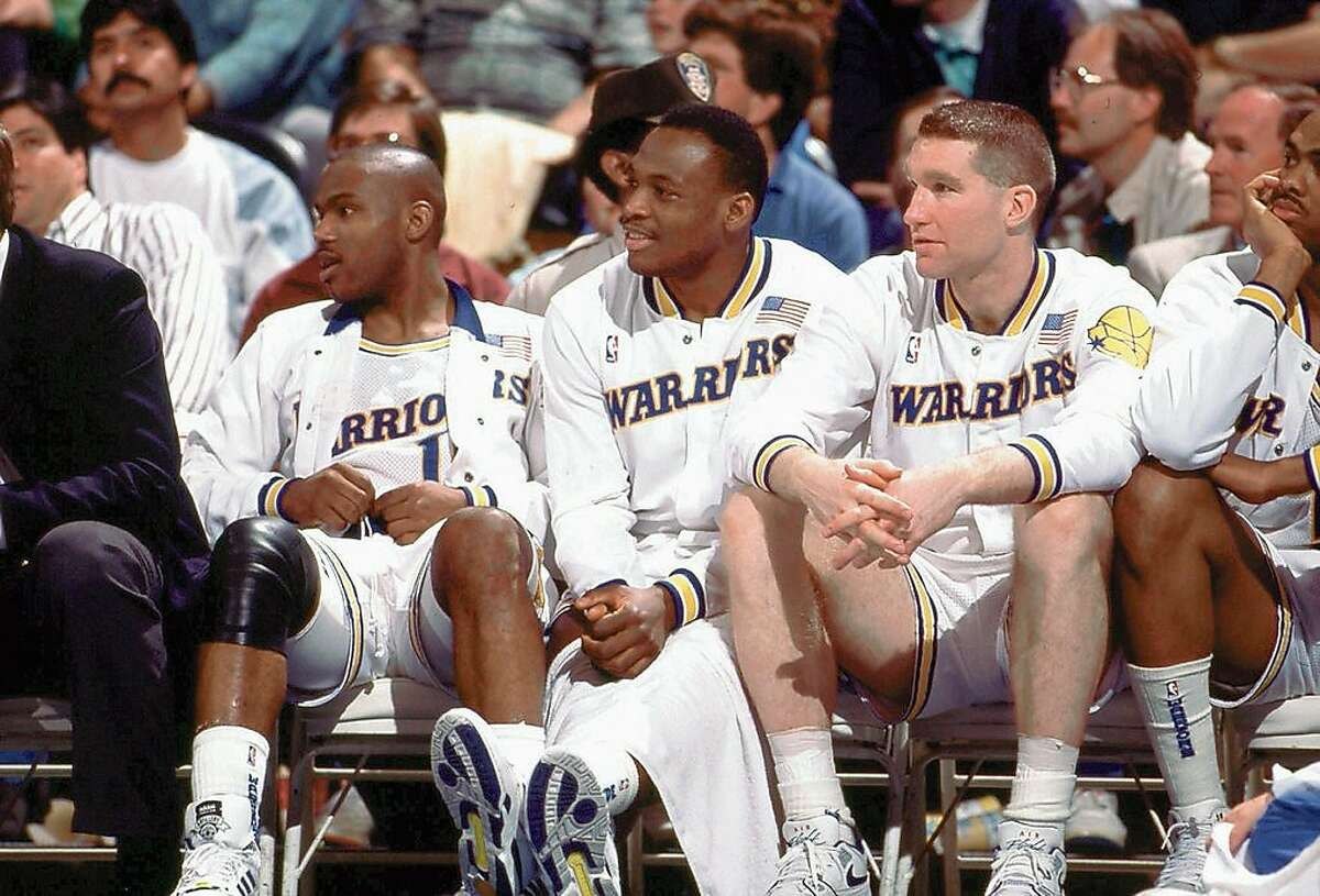 OAKLAND, CA - 1989: (L) Tim Hardaway #10, (C) Mitch Richmond #23 and (R) Chris Mullin #17 of the Golden State Warriors sit on the bench during a game played in 1989 at the Oakland-Alameda Coliseum in Oakland, California. NOTE TO USER: User expressly acknowledges that, by downloading and or using this photograph, User is consenting to the terms and conditions of the Getty Images License agreement. Mandatory Copyright Notice: Copyright 1989 NBAE (Photo by NBA Photos/NBAE via Getty Images)