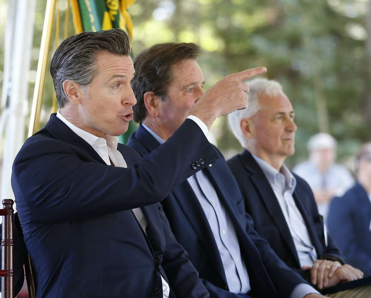 Calif., Gov. Gavin Newsom responds to a group from Butte County calling on him to commit to not accepting campaign money from the Pacific Gas & Electric Co., during the 23rd Annual Lake Tahoe Summit, Tuesday, at South Lake Tahoe, Calif., Tuesday, Aug. 20, 2019. The summit is a gathering of federal, state and local leaders to discuss the restoration and the sustainability of Lake Tahoe. Butte County is where last year's Camp Fire burned through the town of Paradise, killing 86. Newsom met with the group after the summit. (AP Photo/Rich Pedroncelli)