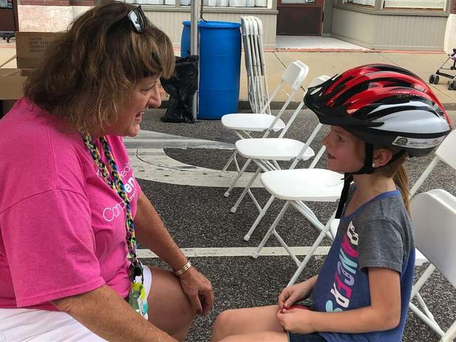 Kim Fanter, Cardinal Glennon, provided the proper fit for the free bicycle helmets that were handed out Saturday at the Criterium. Photo: Julia Biggs | The Intelligencer